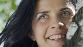 在树附近的微笑的夫人,年轻美女牙微笑,生活幸福喜悦  股票录像