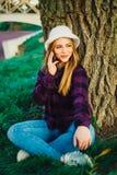 在树附近的白肤金发的女孩谈话在电话 库存图片