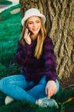 在树附近的白肤金发的女孩谈话在电话 库存照片