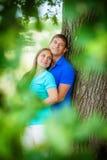 在树附近的年轻爱恋的夫妇 免版税库存照片