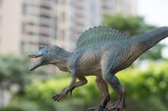 在树&大厦前面的灰色spinosaurus玩具 库存图片