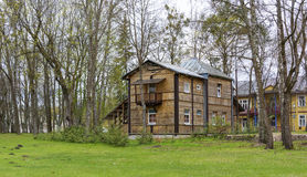 在树建造的两层木房子在绿色草坪附近 图库摄影