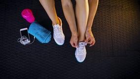 在栓鞋带运动鞋的健身房的地板上安装的适合妇女的顶视图 免版税库存照片