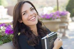 在校园里的微笑的年轻女学生画象 免版税库存图片