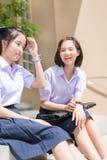 在校服的逗人喜爱的亚洲泰国高女小学生学生夫妇坐聊天与愉快的微笑的和笑的f的楼梯 免版税库存图片