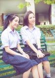 在校服的逗人喜爱的亚洲泰国高女小学生学生夫妇 免版税库存图片