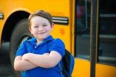在校车前面的愉快的年轻男孩 免版税库存图片