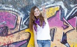 在样式青少年的墙壁附近的女孩街道画 免版税库存图片