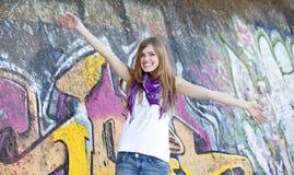 在样式青少年的墙壁附近的女孩街道画 库存照片