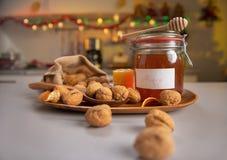 在核桃和瓶子的特写镜头在桌上的蜂蜜 免版税库存照片