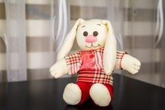 在格子花呢上衣,软的玩具的坐的兔子 免版税库存图片