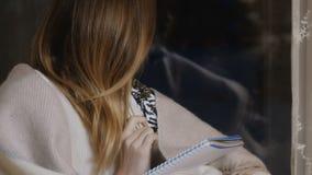 在格子花呢披肩下的俏丽的女孩在笔记本坐窗口基石晚上并且写 股票录像