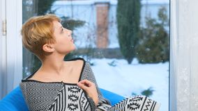 在格子花呢披肩下的少妇在窗口附近坐并且享受看法 影视素材