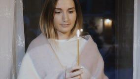 在格子花呢披肩下的美丽的女孩有反对夜窗口的灼烧的蜡烛的 股票录像