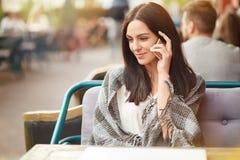 在格子花呢披肩包裹的可爱的女性,通过有最好的朋友的手机享受交谈,花费业余时间在舒适自助食堂, enjo 库存照片