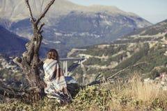在格子花呢披肩包裹的女孩坐与一杯咖啡的一棵树和看城市 格子花呢披肩的一个女孩在villag对面 免版税图库摄影
