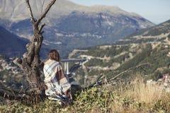 在格子花呢披肩包裹的女孩坐与一杯咖啡的一棵树和看城市 格子花呢披肩的一个女孩在villag对面 库存图片