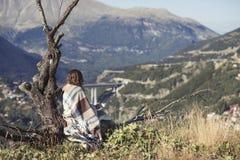 在格子花呢披肩包裹的女孩坐与一杯咖啡的一棵树和看城市 格子花呢披肩的一个女孩在villag对面 图库摄影