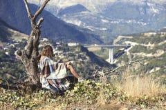 在格子花呢披肩包裹的女孩坐与一杯咖啡的一棵树和看城市 格子花呢披肩的一个女孩在villag对面 库存照片