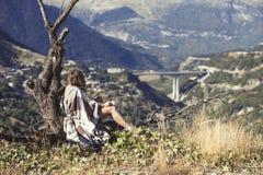 在格子花呢披肩包裹的女孩坐与一杯咖啡的一棵树和看城市 格子花呢披肩的一个女孩在villag对面 免版税库存图片