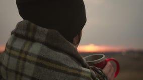 在格子花呢披肩包裹的年轻旅客女孩放松与杯子饮料在日落 寂寞,自由,孑然概念 股票视频