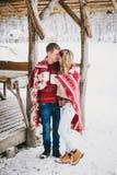 在格子花呢披肩包裹的愉快的夫妇在一个多雪的森林里喝热的茶 免版税库存照片