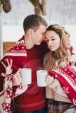 在格子花呢披肩包裹的愉快的夫妇在一个多雪的森林里喝热的茶 库存照片
