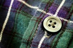 在格子花呢披肩法绒衬衣的按钮 图库摄影