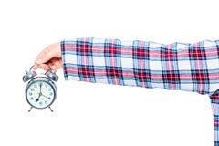 在格子花呢披肩睡衣的手有在白色的一个闹钟的 库存图片
