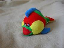在格子花呢披肩背景的玩具鱼 免版税库存照片
