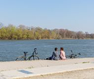 在格子衬衫的浪漫年轻夫妇坐有自行车的河岸 活跃生存概念 文本的空间 免版税图库摄影
