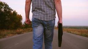 在格子衬衫的男性商人沿有黑公文包的一条柏油路在手中走有文件的 r 免版税库存照片