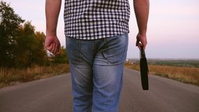 在格子衬衫的男性商人沿有黑公文包的一条柏油路在手中走有文件的 r 免版税库存图片