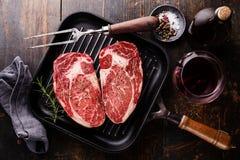 在格栅平底锅的未加工的新鲜的肉牛排Ribeye在木背景 免版税图库摄影