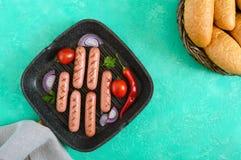 在格栅平底锅的水多的烤香肠有菜和酥脆小圆面包的 顶视图 免版税库存图片