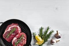 在格栅煎锅的未加工的牛排用草本和油在白色背景,顶视图,地方文本的 免版税库存照片
