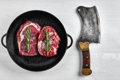 在格栅煎锅的未加工的牛排用草本和油在白色背景,顶视图,地方文本的 库存图片