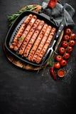 在格栅煎锅的烤香肠多味腊肠在黑背景 顶视图 传统德国烹调 免版税库存照片