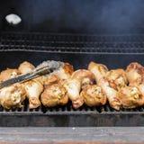 在格栅的开胃火鸡鼓槌,在与火和烟特写镜头的木炭火炉 概念夏天野餐 免版税库存照片