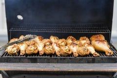 在格栅的开胃火鸡鼓槌,在与火和烟特写镜头的木炭火炉 概念夏天野餐 图库摄影