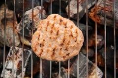 在格栅的汉堡包与煮熟的跳舞火焰 免版税库存照片