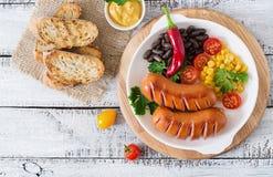 在格栅的香肠与在盛肉盘的菜 顶视图 库存照片