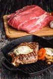 在格栅铁平底锅的烤黑安格斯牛排在木黑背景以未加工 库存图片