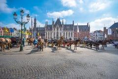在格罗特Markt的马支架在中世纪城市布鲁基在早晨,比利时摆正 库存照片