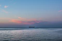 在桃红色云彩-日出/日落下的海船 库存照片