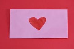 在桃红色信封的红色心脏在颜色泡沫板 免版税库存图片