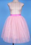 在桃红色公主裙子的时装模特在蓝色背景 免版税图库摄影