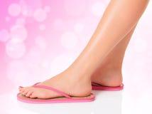 在桃红色凉鞋的女性英尺 免版税库存照片