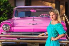 在桃红色减速火箭的汽车附近的微笑的女孩 免版税库存图片