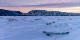在桃红色口气的冬天风景与在冻河的山脊冰日落的 库存照片
